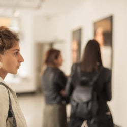 woman studying a painting at an art gallery